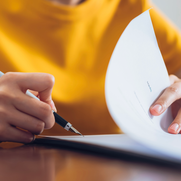 Une personne signe des documents